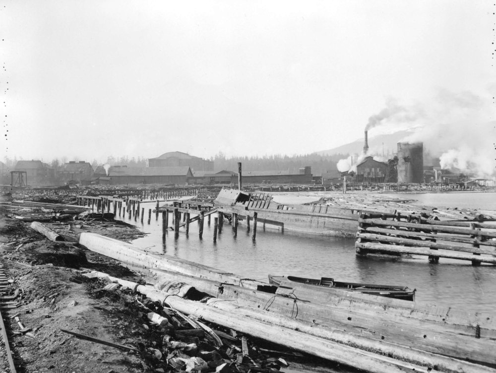Looking West across Coal Harbour in 1925 with Brooks Iowa Lumber Co on the right and Denman Arena in the distance. Source: The City of Vancouver Archives Reference Code: AM54-S4-: Bu N38 Item : Bu N38 - [View of Coal Harbour looking west from the foot of Broughton Street]
