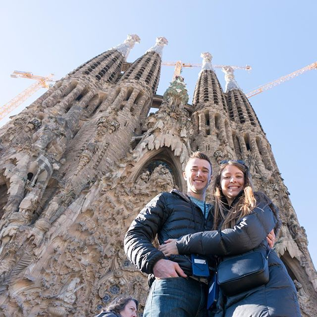 Day 169: Snugglin' at the Sagrada Família. ⛪ We were awestruck by this iconic church in Barcelona. It's very different from other cathedrals in Europe. Antoni Gaudí started designing the church in the late 1800s and he used inspiration from nature for its structure and decor. When you walk inside, there are a series of tall columns that branch off toward the ceiling to resemble a forest. On the walls, there are massive stained glass windows that bathe the church in colorful light. One wall has cool tones while another has warm tones. This accentuates the colors of sunrise and sunset, so the cathedral has a very different ambiance throughout the day. It was so beautiful and we didn't want to leave! #365daysoftravels