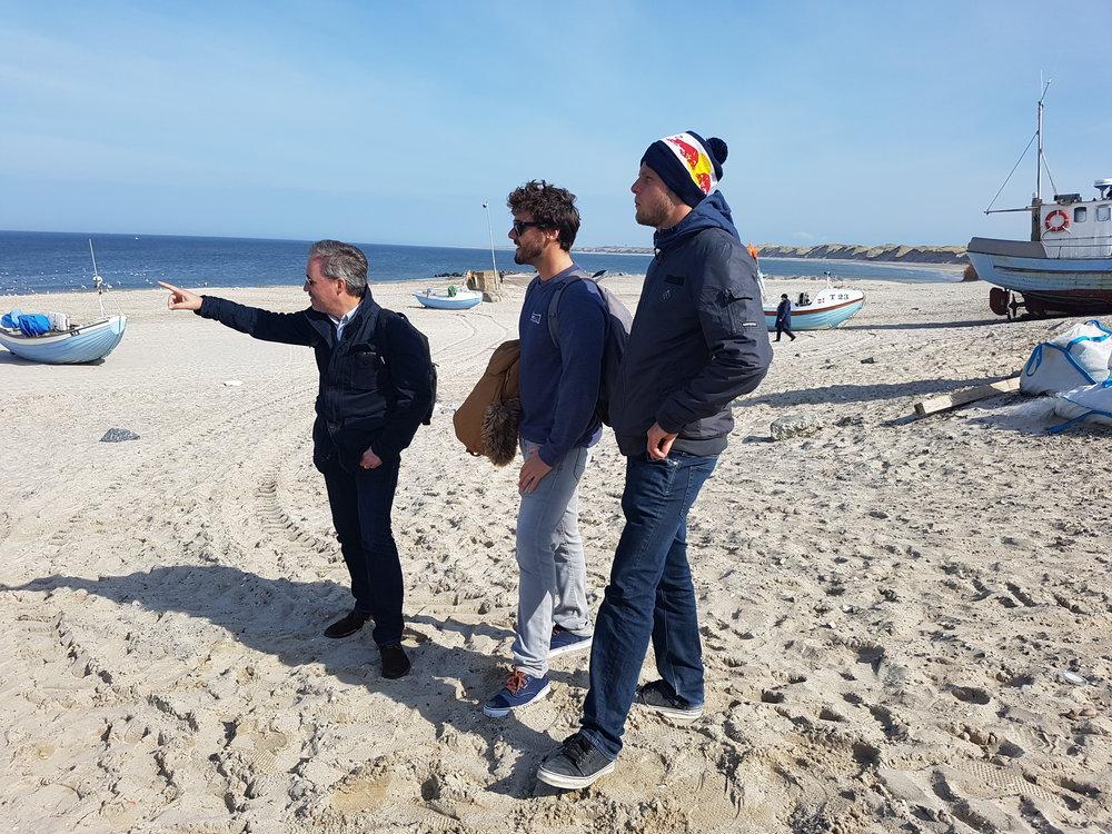 Klitmøllersurferen og den tredobbelte verdensmester i Stand Up Padling viser Vorupør frem for direktøren for det internationale surfforbund (ISA) Robert Fasula og eventchefen Harrison Robbs