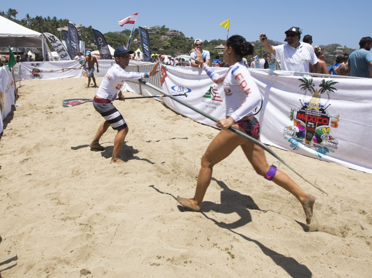 Relay - The relay race takes place on a rectangular course. There are four athletes per nation on each team. Each team is made up of two women and two men. The competition begins at a start and exchange zone on the beach. From here, the first athlete runs to the shore, jumps on the board, and paddles out and around the two buoys. When the athlete lands on the beach, he or she runs to the exchange zone and taps the next athlete on his or her hand, after which the next athlete completes the course and so on.