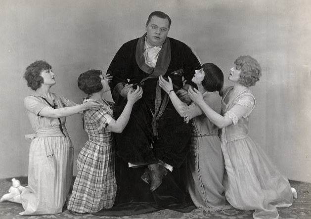 Portrait of Roscoe 'Fatty' Arbuckle wearing a smoking jacket and surrounded by kneeling young ladies, c. 1918
