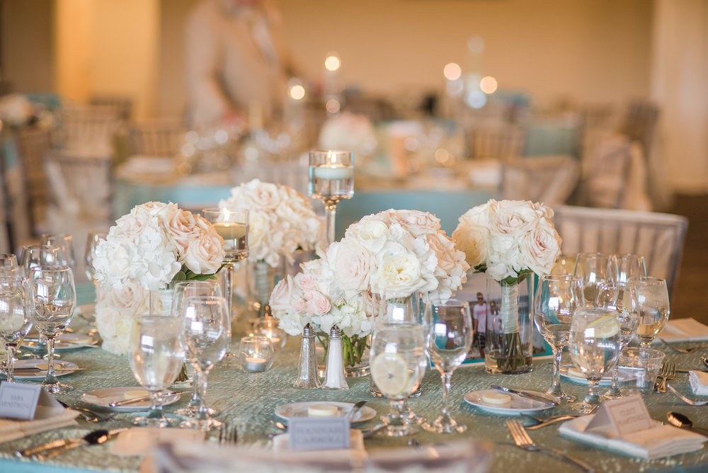 So much attention to detail went into this weeding. The small, low bouquets of ivory and blush roses, the framed photos of the couple on each table, the tented place cards that were color coded to indicate the guest meal choice.... perfection!