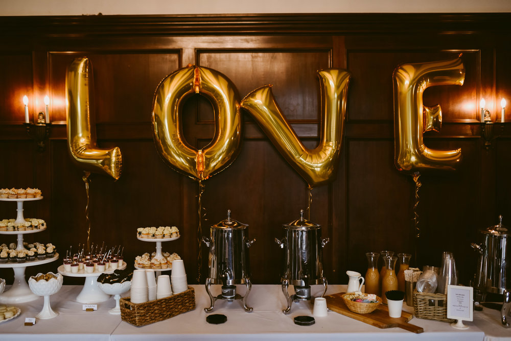 These fun gold word balloons have been trending for a while now, and we LOVE the whimsy they bring to any event! These are so classy against the rich dark wood wall.