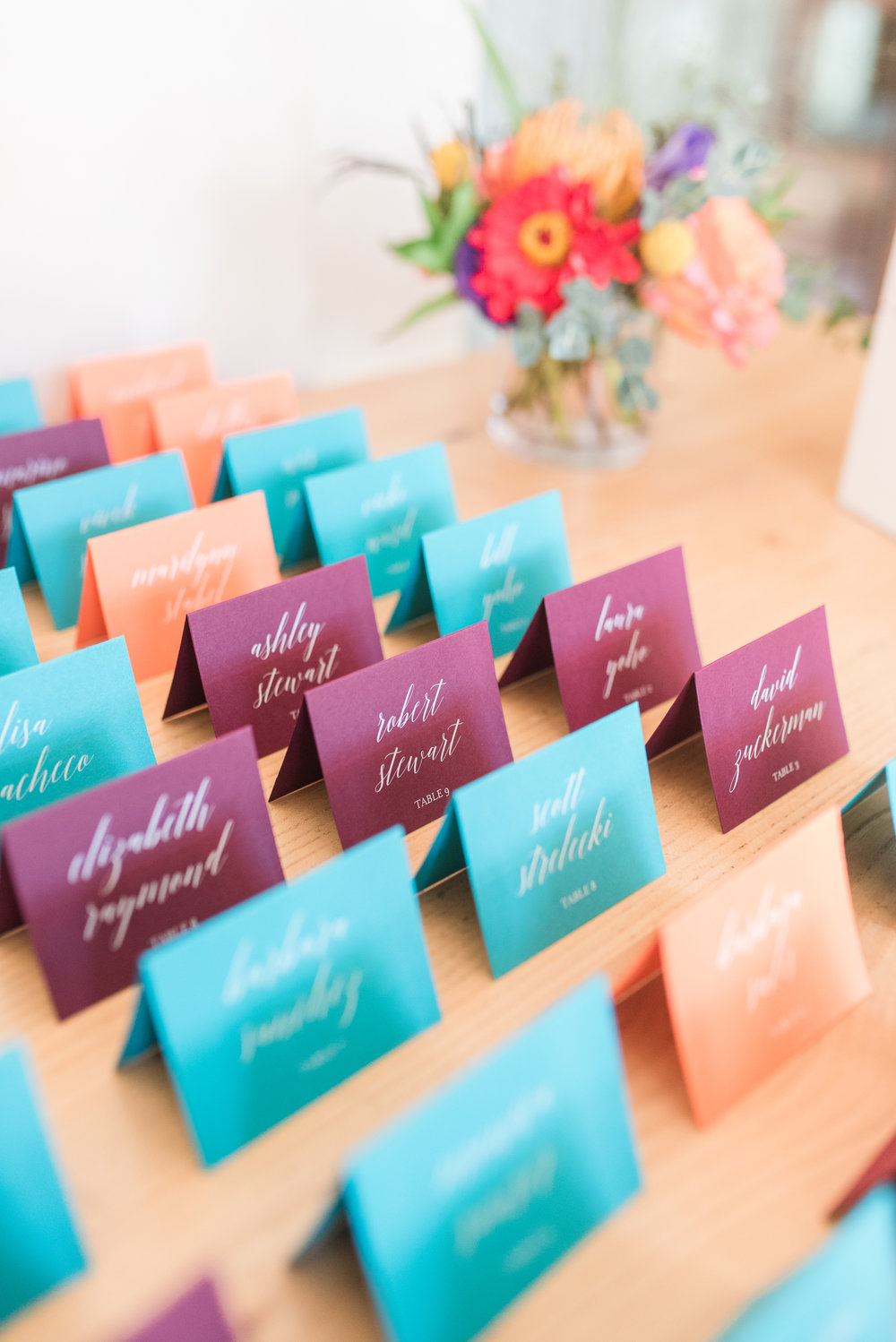 Alissa and Clint opted for color-coded escort cards for their reception, which were fun and fresh with white ink printing! Photo © Maura Jane Photography 2018