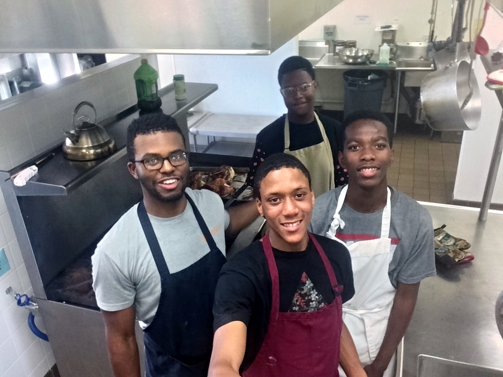 Milton (left) with Dj (center Background) and other members of Urban Hope's Young Leaders Group cooking dinner before our biweekly meeting.
