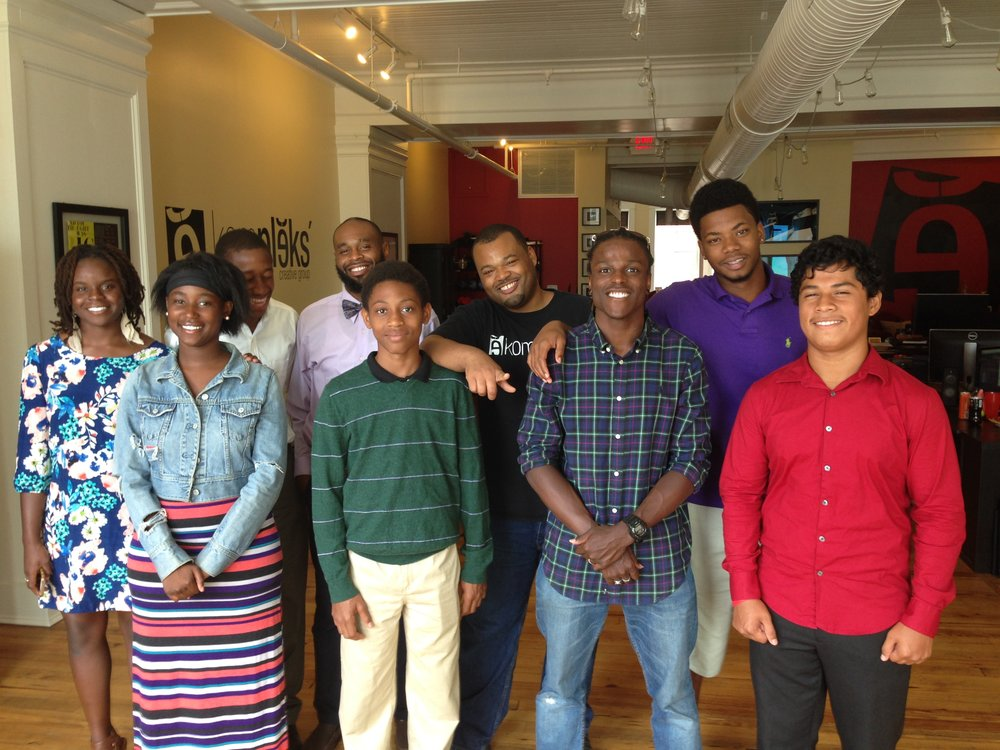 Summer camp assistant director Isaiah Simms (bow tie), counselor Frank Smith (blue plaid), and CIT Demicheal Burton (purple) with youth during a small business field trip at Kompleks Creative design firm