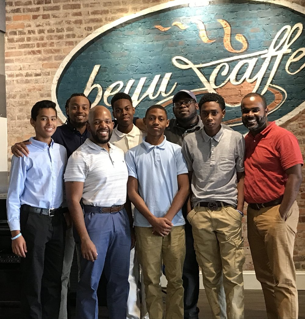 Robert (third from the right with hat & glasses) poses with the walltown's finest track at beyu caffe with owner dorian bolden as they prepared for their  next gen entrepreneurship challenge