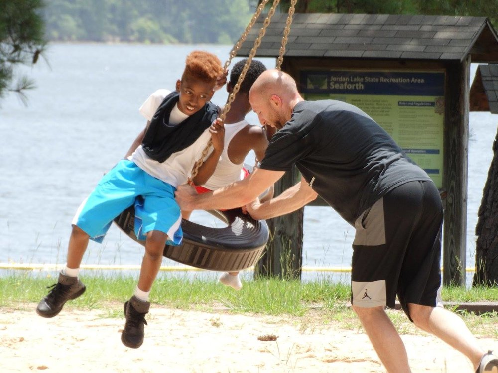 Isaiah and a fellow camper going for a good swing with Summer Camp Director Dan Keegan
