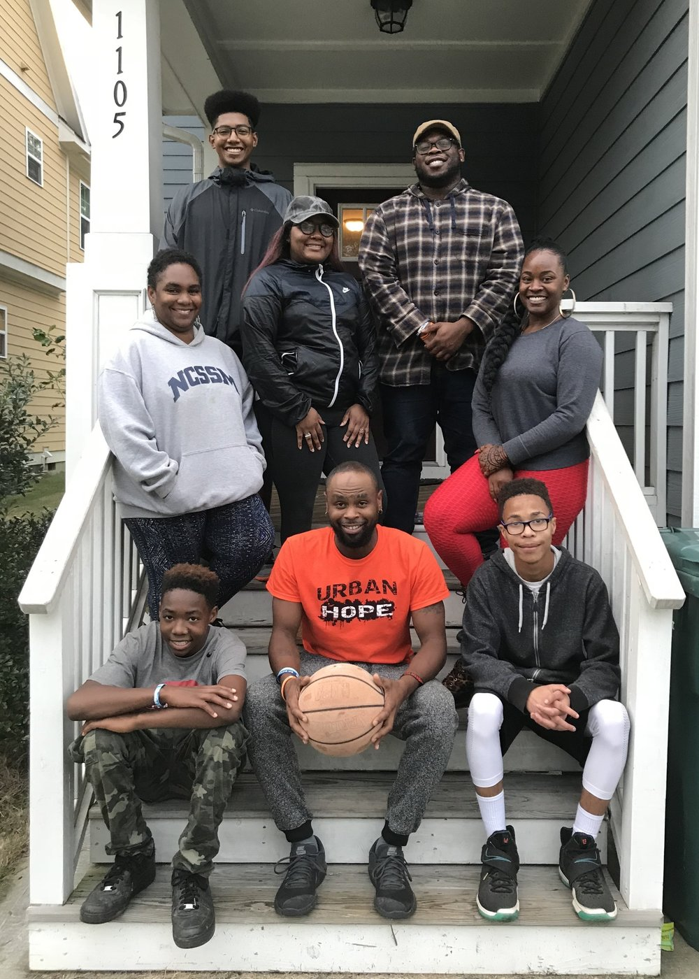 Robert (top right), Jennifer (far right), and Isaiah (ball in hand) outside of The Alexander House with a spiritual mentor, other young adult leaders and neighborhood youth