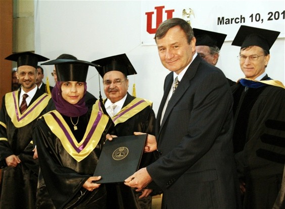 U.S. Ambassador to Afghanistan Karl Eikenberry presents a graduate with her Master's of Education diploma. (USAID)