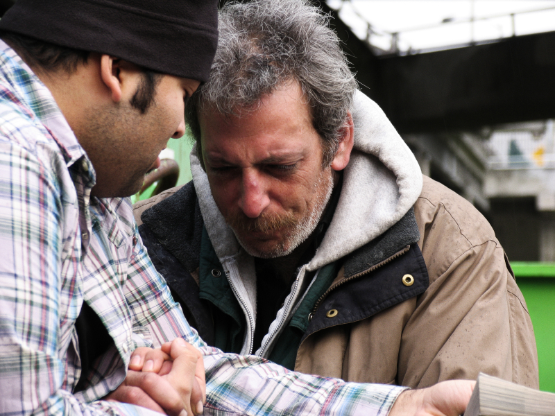 A young man prays with a homeless man.