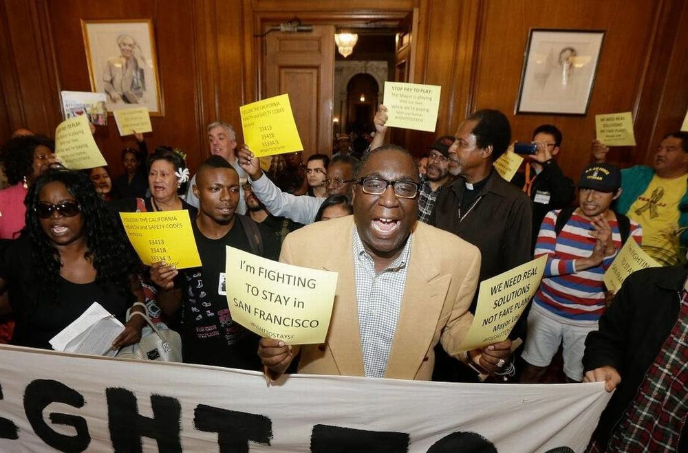 Pastor Yul Dorn, center, yells as he and others protest evictions at San Francisco City Hall in 2015 as African-American homeownership rates have dropped. Jeff Chiu Associated Press file