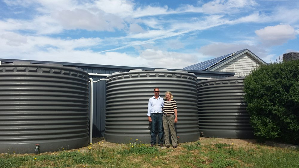 A couple show off their water cisterns in front of their home in Australia. (Photo courtesy WATERAUSTRALIA)
