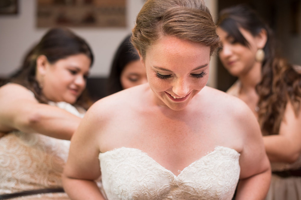 13 Brittney's bridesmaids helping her put on her dress.jpg
