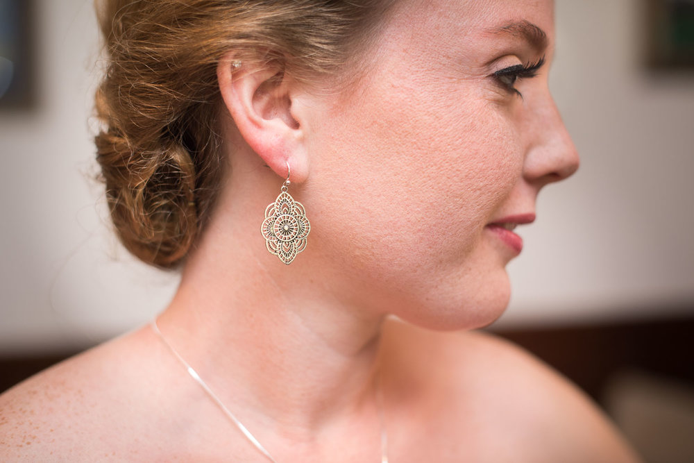 19 brittney puts on her wedding day earrings.jpg