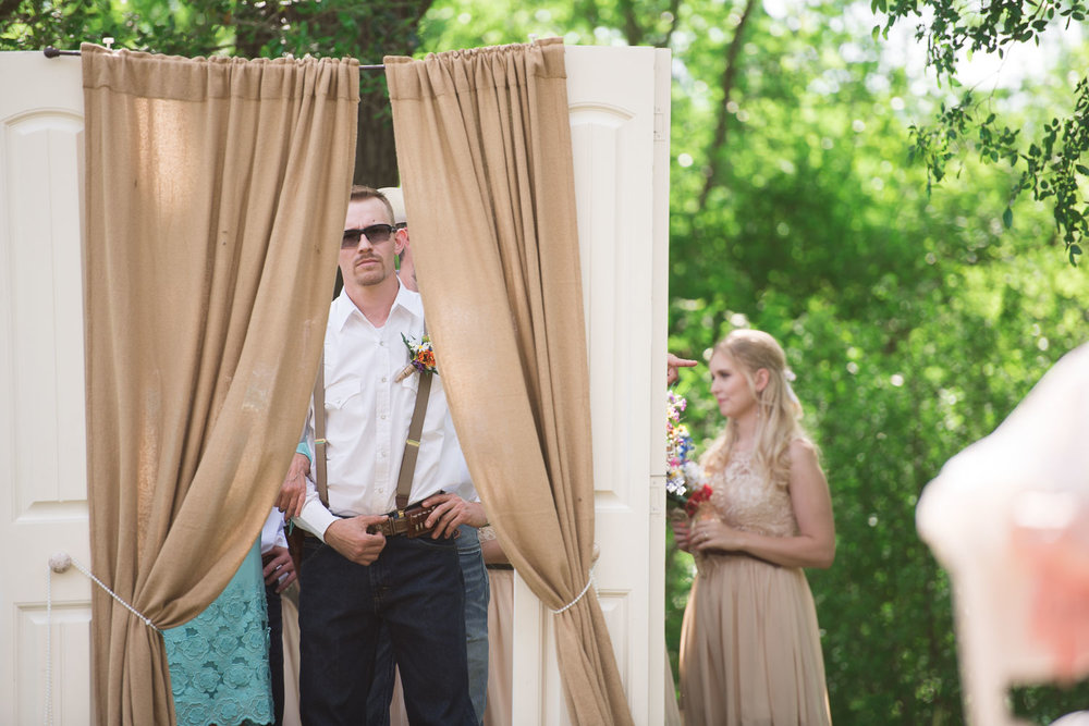 23 Groom peers through curtain as he waits to come down the aisle.jpg