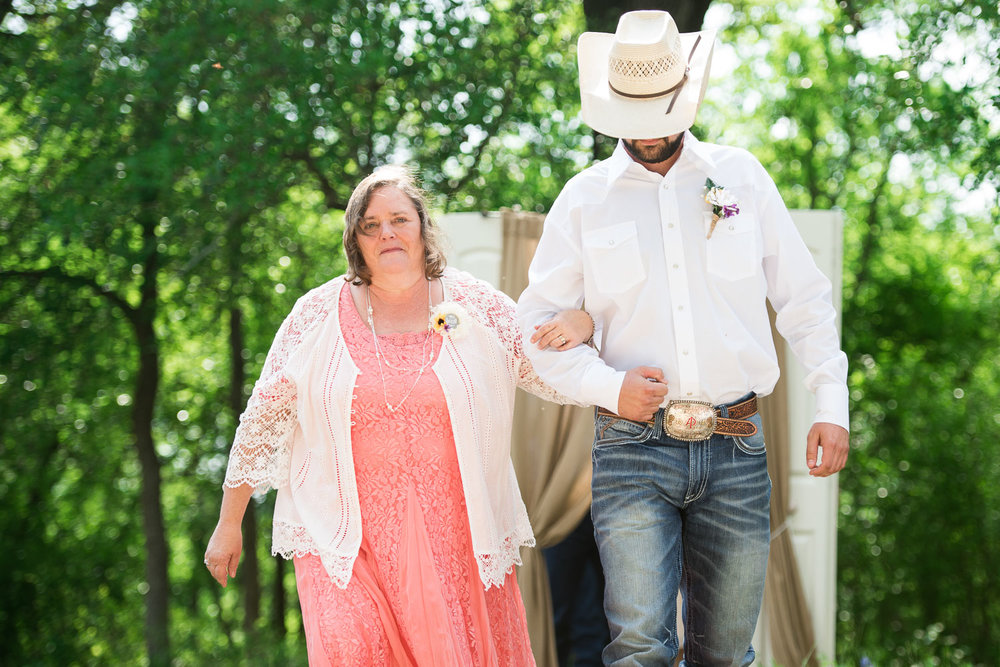 26 Mother of the bride is ushered down the aisle by the groomsman in a cowboy hat.jpg