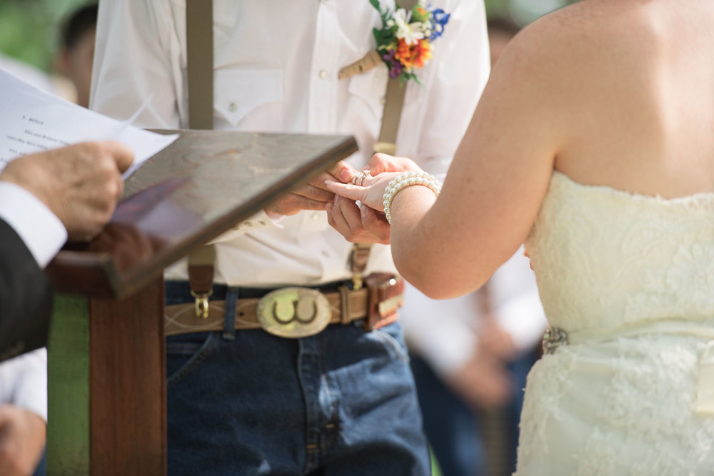 50 Bride and groom exchanging wedding bands during wedding ceremony on watson family ranch.jpg