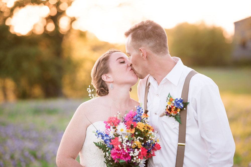 95 bride and groom kissing during sunset on family farm.jpg
