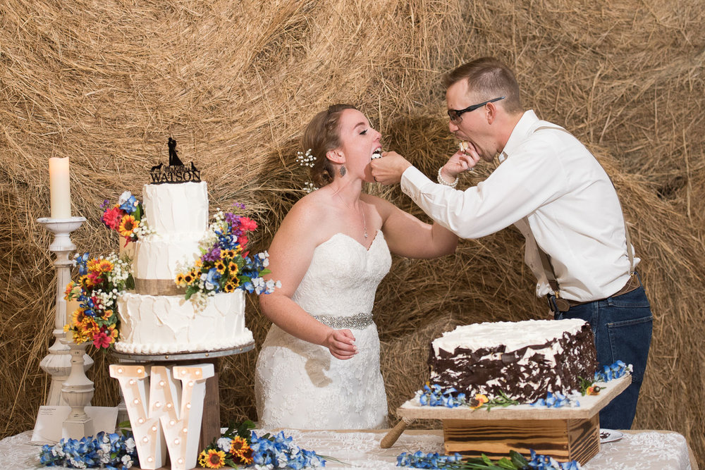 119 couple sharing their first bite of cake during reception.jpg
