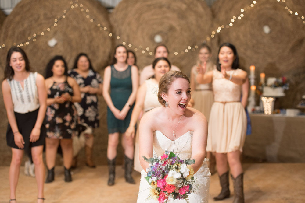 121 bride tosses bouquet to girls in barn wedding.jpg
