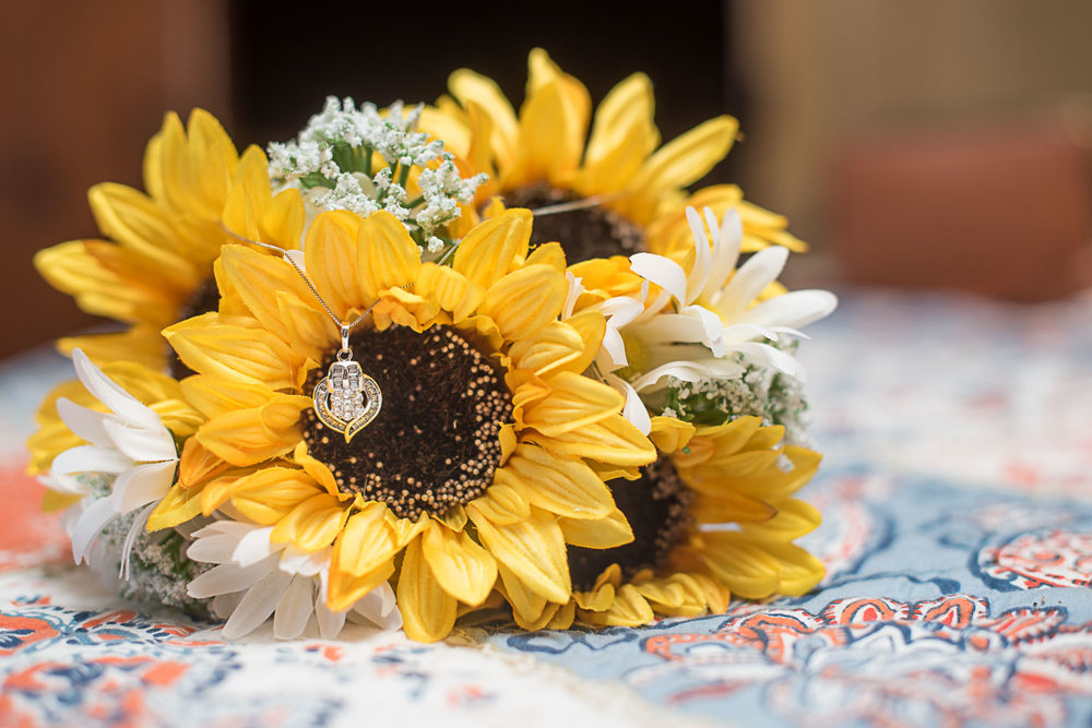 3 bride's wedding necklace on sunflower bouquet.jpg