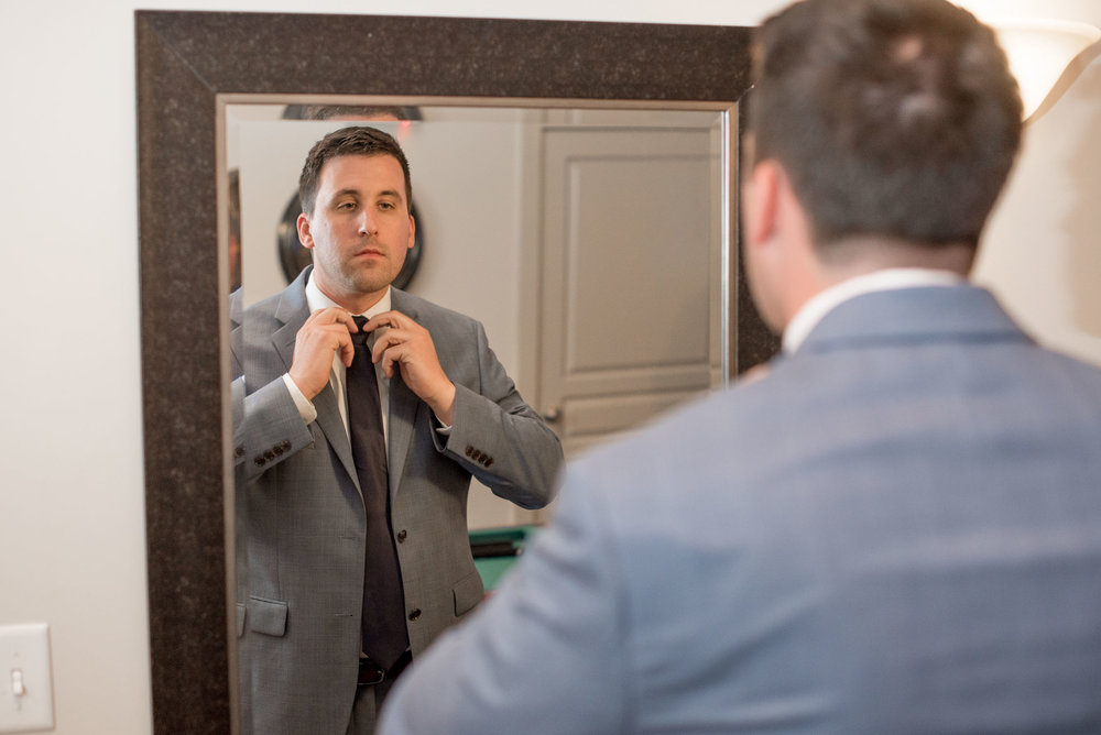 30 groom getting ready in the mirror before wedding.jpg