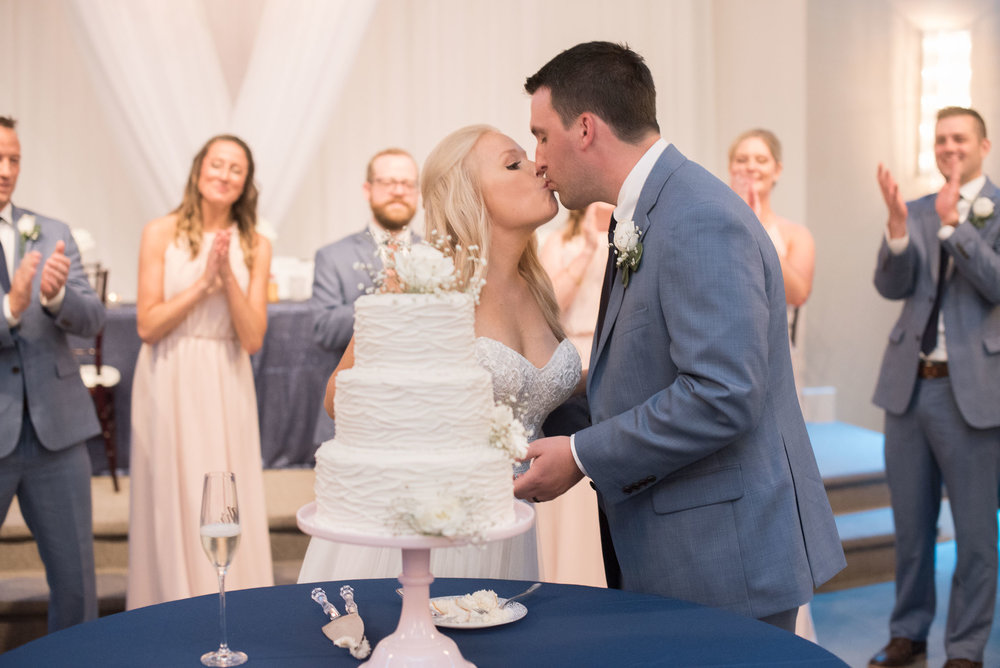 128 bride and groom kissing during cake cutting.jpg