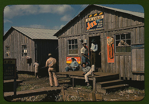 "Migratory laborer outside of a ""juke joint"" during a slack season, Bella Glade, Florida. Photographed by Marion Post Wolcott."