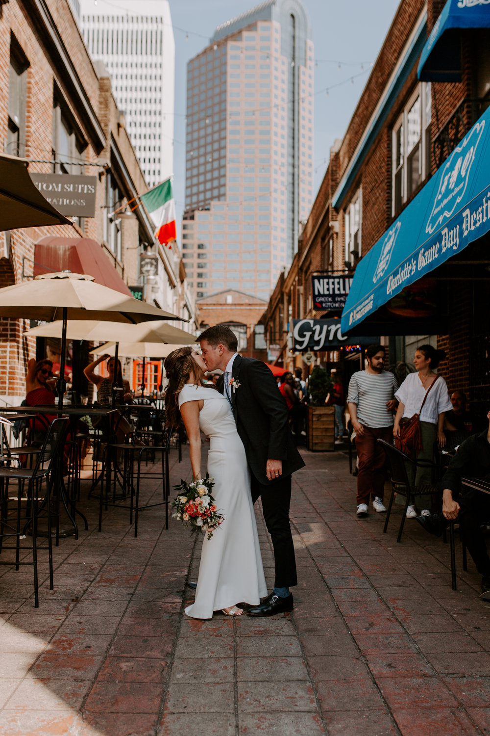 engagement photography in Uptown Charlotte for an Engagement session while kissing