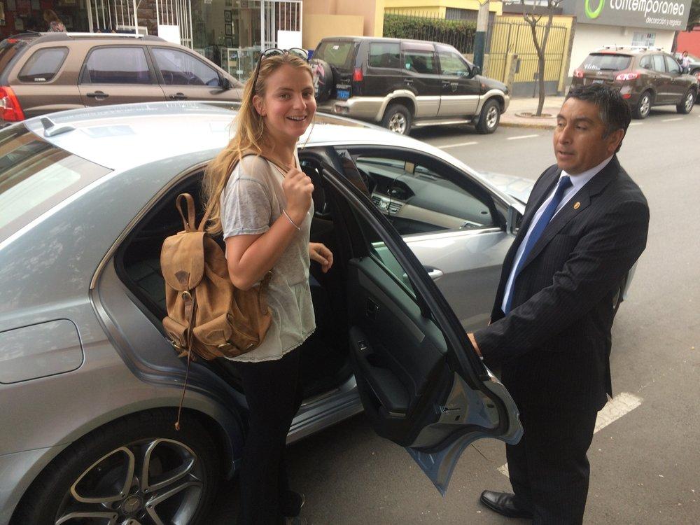De deur wordt voor dido opgehouden door de chauffeur en bodyguard van roberto