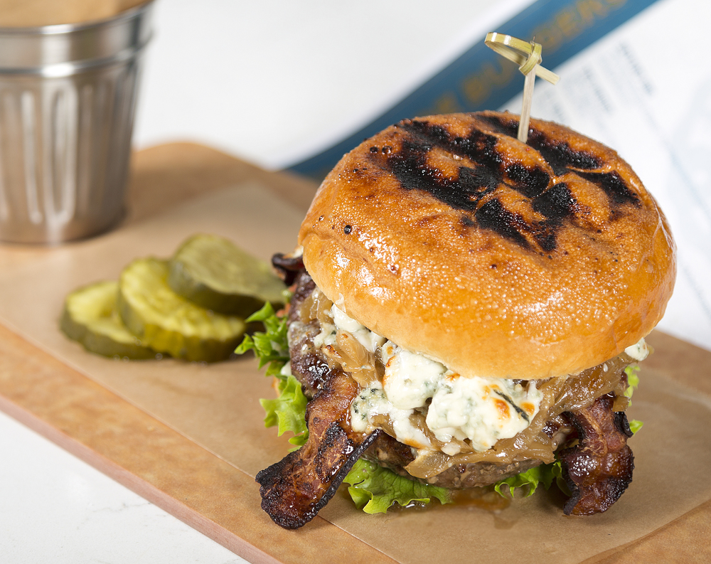 BLACK 'N' BLUE   Signature Custom Blended Beef Grind, Cajun Spice, Caramelized Onions, Artisan Field Greens, Bacon, Blue Cheese, Garlic Mayo, Toasted Brioche