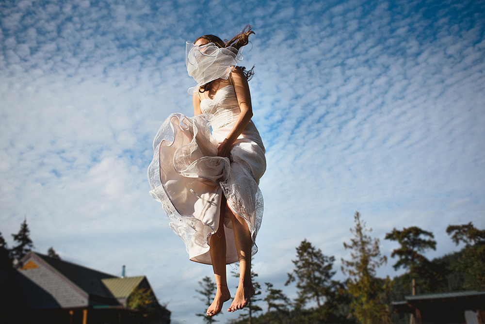 bride jumping with vail covering her face, gulf islands BC