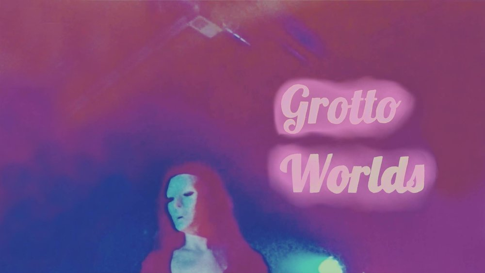 "[image] Grotto Worlds poster. Text with cursive-like letters read ""Grotto Worlds."" Blurry purple and blue background. A small air vent. A masked figure with long hair."