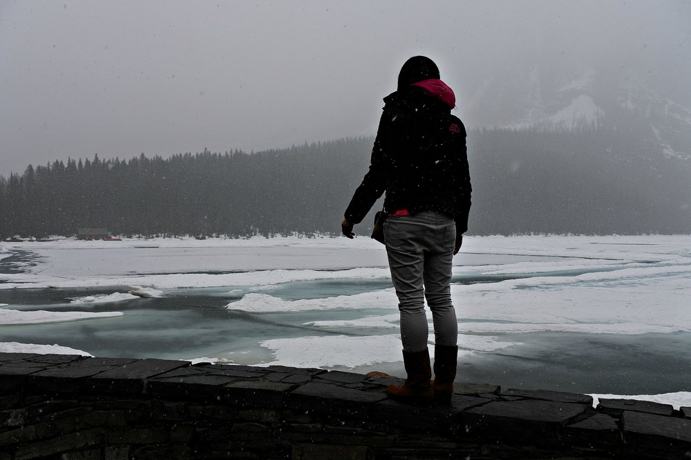 Enjoying a moment of solitude in the semi-frozen and stillness of Lake Louise in Banff, Canada