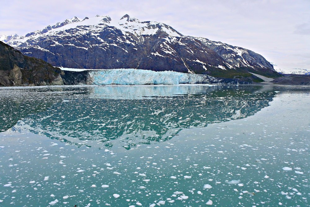 "Glacier Bay, Alaska. The block of blue ice beneath the mountain is a glacier. The white fluff on the water are pieces of ice that broke away from the bigger block during a process called ""caving"""