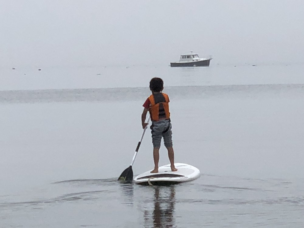 paddleboarding in the ocean in Maine