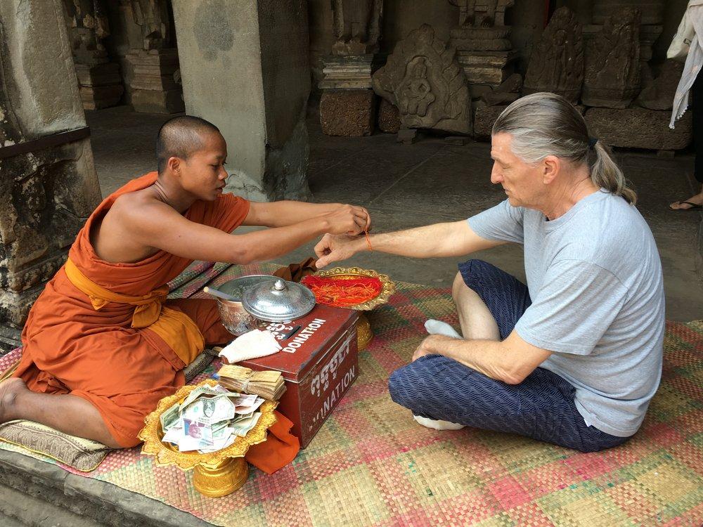 バイヨン遺跡にて。僧侶に祝福をしていただきました。