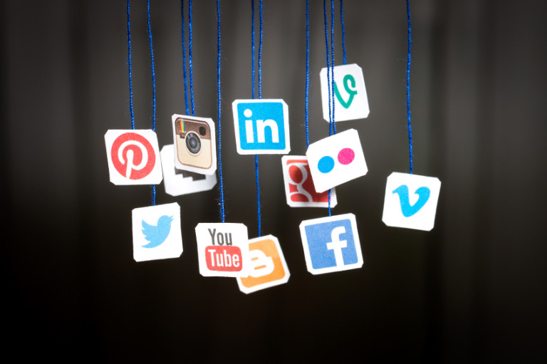 Popular social media website logos printed on paper and hanging
