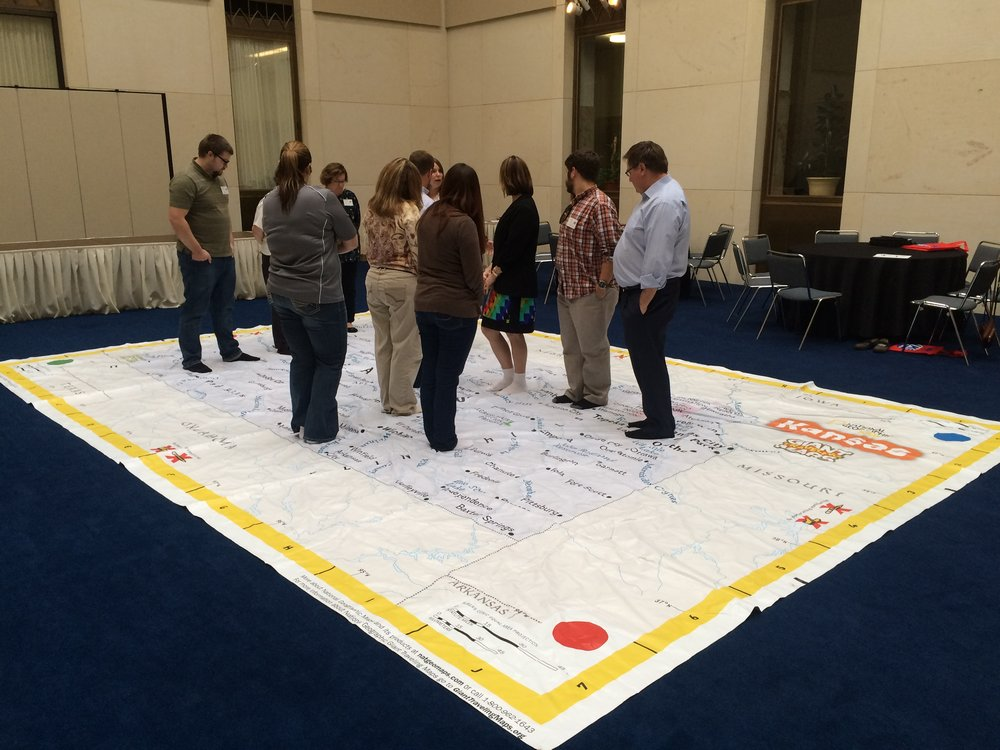Teachers interacting with the Giant State Map of Kansas at the Kansas Social Studies Conference.