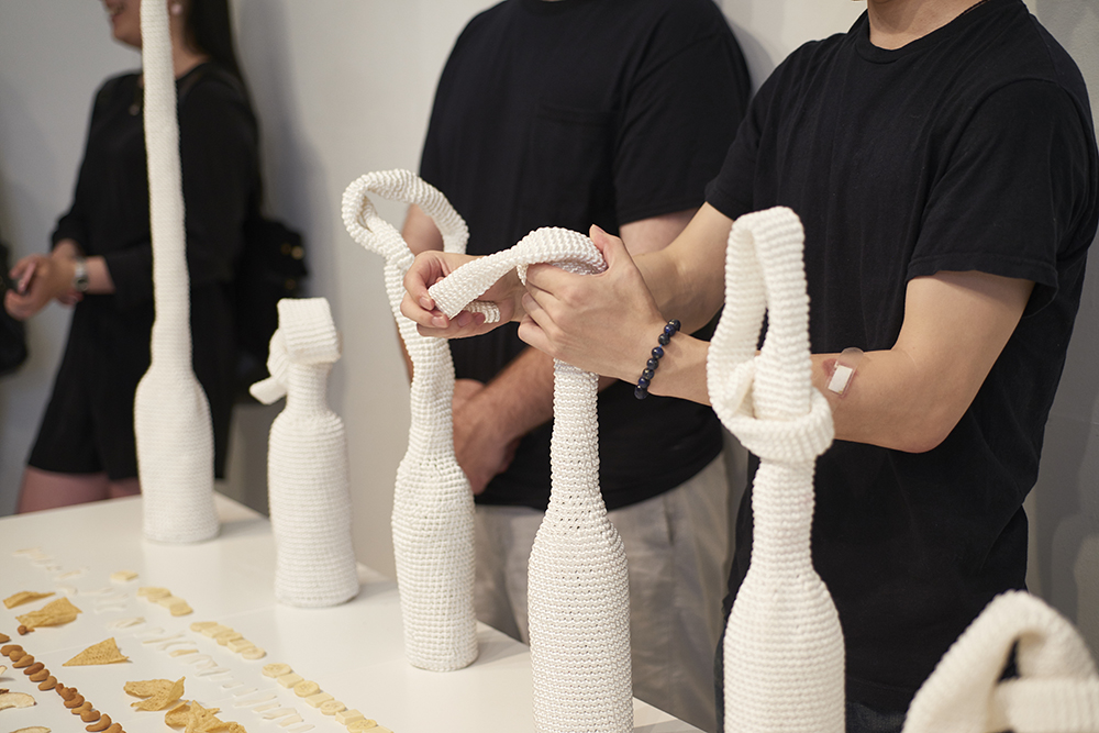 manipulating the artworks (tie-shape  bottle covers)