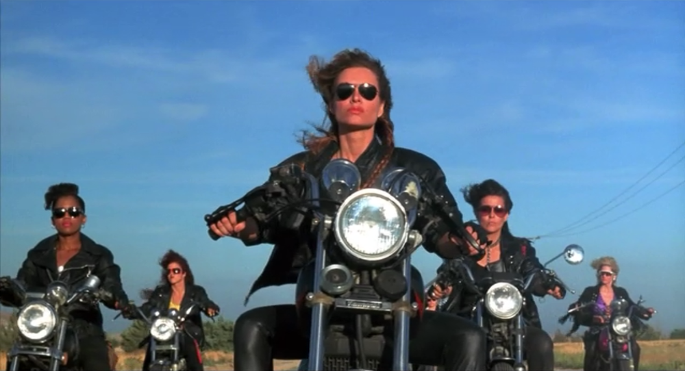 "Got A Girl Crush On: Women of the Wolf (Easy Wheels, 1989). Bikers, big hair and baby theft. The babes of (what is easily my new favorite movie) Easy Wheels (1989) won me over within the first minute of this amazingly campy 80's flick. Abandoned by her parents and raised by wolves, She Wolf and the gang cruise around the state, um, ""acquiring"" baby girls. Terrible, perhaps. Not to worry, there are perks to a forced wolf pack up-bringing. All Women of the Wolf really want is to raise a tribe of strong independent women who are ""Fearless, wild and free!"" You. are. welcome."