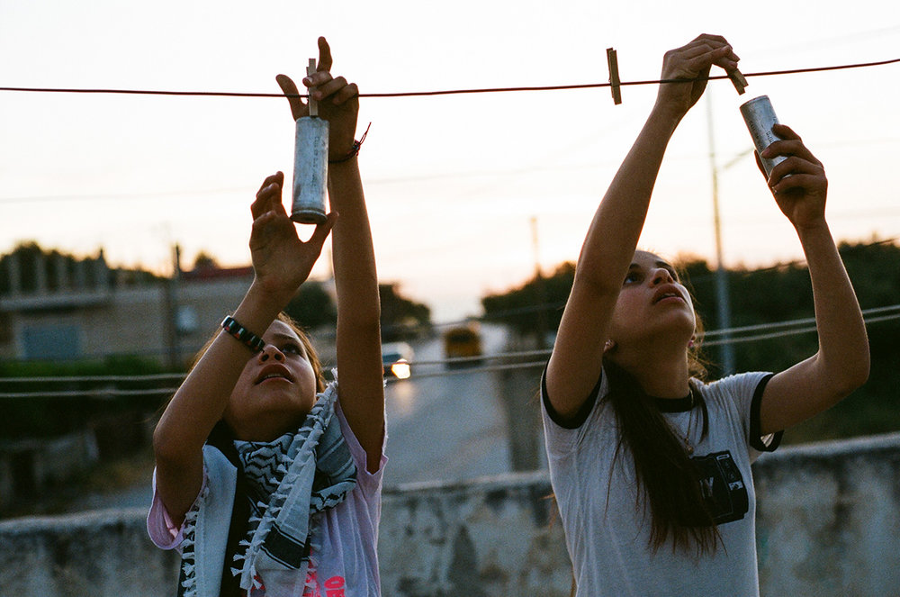 Janna Ayyad and Rand Tamimi on the roof above their home in Nabi Saleh. Their home is littered with hundreds of teargas canisters that have been launched at their home over several years. The children have turned them into play things that they kick around like soccer balls or throw potatoes at.
