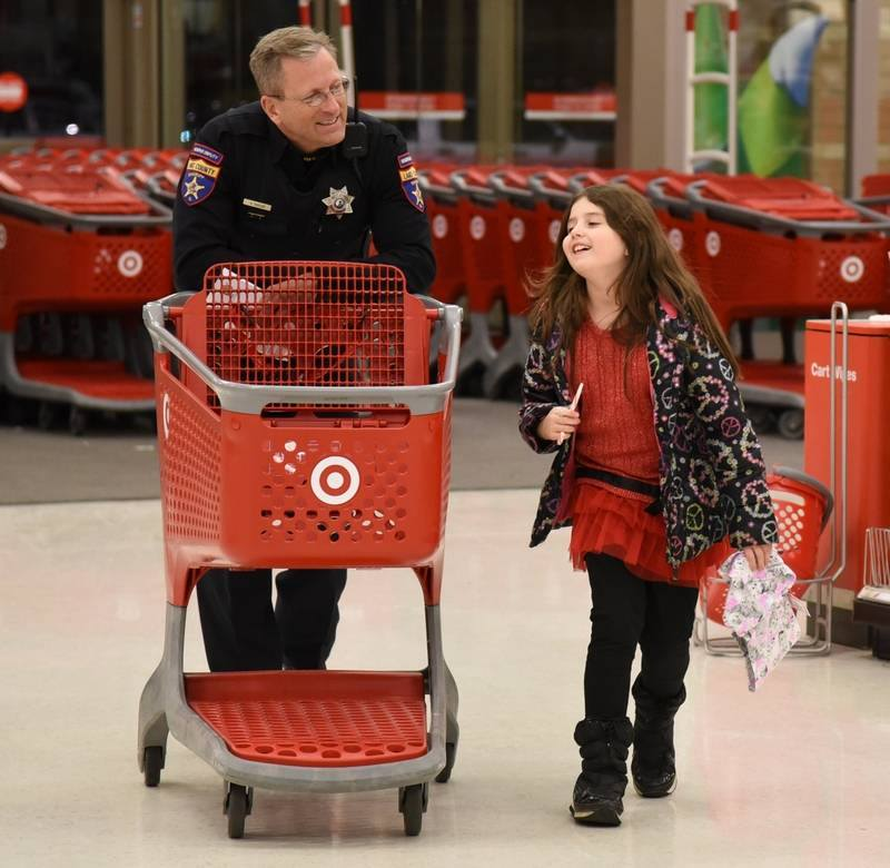 Lake County Sheriff's Reserve Deputy Stan Taylor has fun with Gavin Central third grade student Chevelle Reilly during Tuesday's Lake County Sheriff's Association 4th annual Shop with a Sheriff event at the Mundelein Target. Paul Valade | Photographer