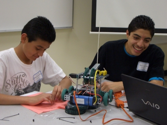 This pair of students has their robot seemingly build, but must get their code working right, hence the laptop on the table. Building the robot is the best hands-on activity, while coding it flexes the mental muscle needed to make the robot do what it is supposed to.