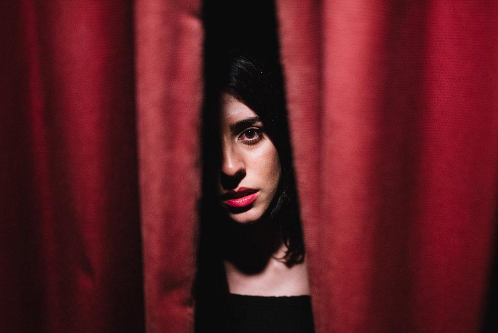 mujer-morena-saliendo-de-cortinas-rojas.jpg