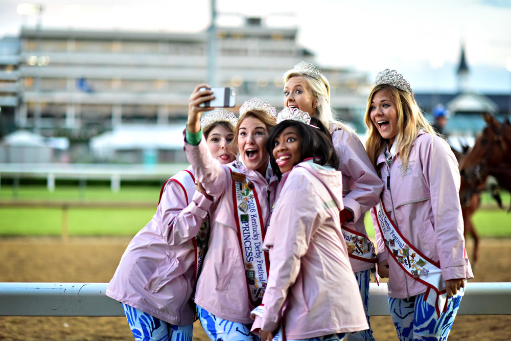 "Kentucky Derby Festival princesses pose along the backside at Churchill Downs on Thursday. Festival princess Adrienne Poole, standing middle back, says, ""Watching the sunrise this morning along the track at Churchill Downs was icing on the cake and really an experience I'll never forget, so we had to take a selfie."""