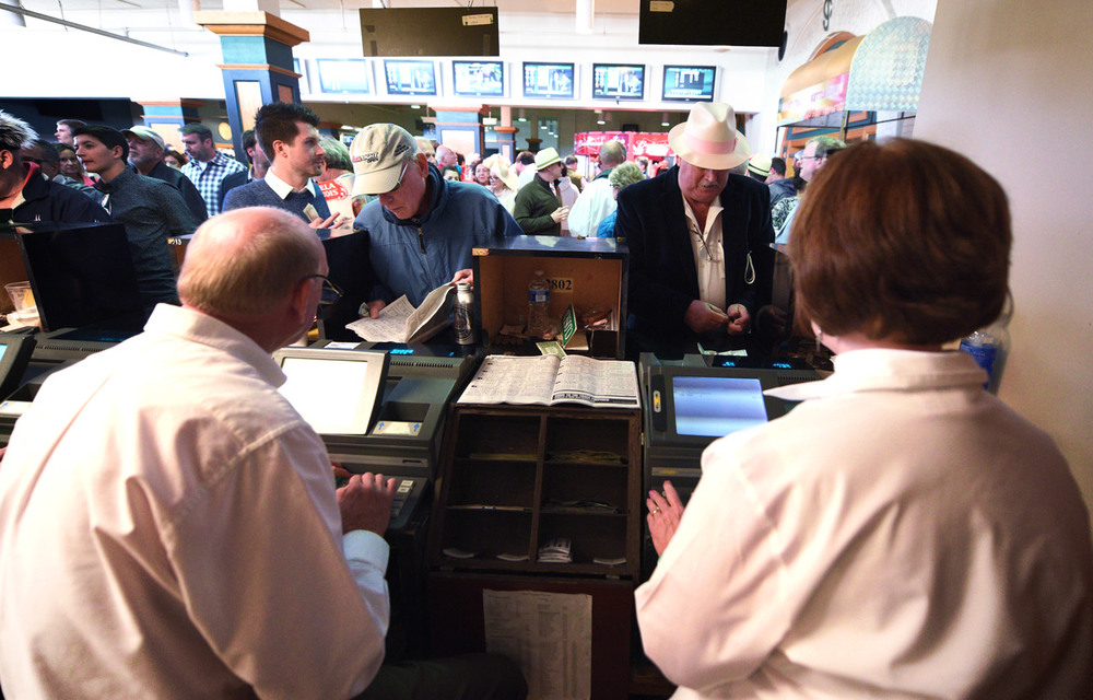 Teller Terry Smith, right, takes a bet at a betting window on the Thursday before Derby Day. An estimated $12 million was bet on last year's Kentucky Derby at Churchill Downs, and millions more are wagered off site.