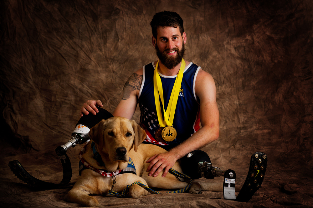 Stefan Leroy, 25, sits with his service dog, Knoxville. Leroy served in the Army and is from Santa Rosa, California, but now resides in Jupiter, Florida. He won a gold medal in sitting volleyball.