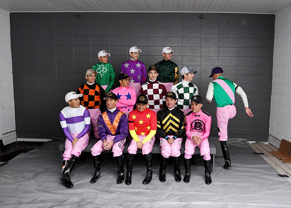Jockeys riding in the Kentucky Oaks race pose for a group portrait at Churchill Downs on Friday. Hernandez is in the purple silks with silver stars.